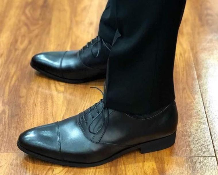 黒のスーツ、黒の内羽根ストレートチップ着用。 シングル仕上げ。(裾のアップ)