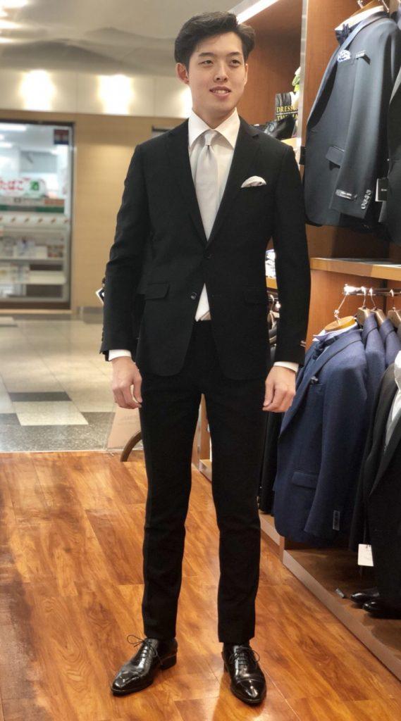 ブラックスーツに白シャツ、シルバーソリッドタイを着ている谷口さん