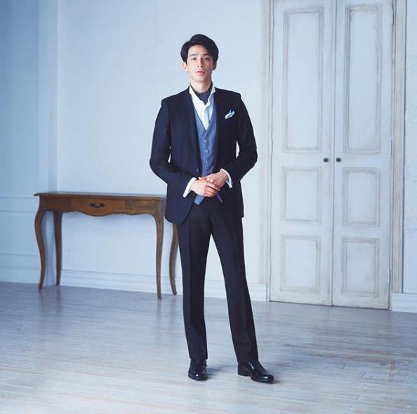 ブラックフォーマル(礼服)にライトグレーのベスト(ジレ)、白のウイングカラーシャツにアスコットスカーフ、黒のストレートチップの革靴