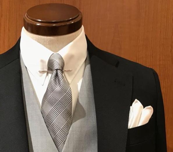 ブラックスーツにライトグレーのベスト(ジレ)、白無地のシャツ、グレナカートチェックのネクタイ、シルバーのカラーピン、白のシルクのチーフ