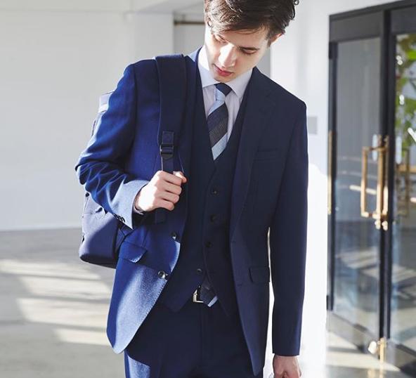 ブルーバーズアイスリーピーススーツにパープルのセミワイドカラーシャツ、ネイビー&ブルー&グレーのレジメンタルタイ