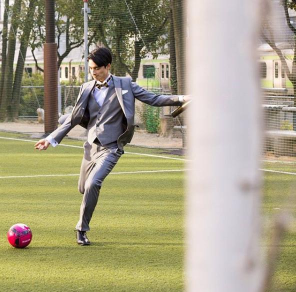 ライトグレーのスーツにライトグレーのベストを着用して芝生でサッカー(ボウタイにポケットチーフ着用)
