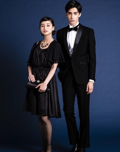 女性 ブラックのサテン地のワンピースドレスに黒のクラッチバッグ。男性 黒のショールカラータキシード、白のウィングカラーシャツ、黒のベルベットのボウタイ