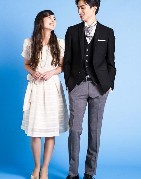 女性ホワイトベージュのワンピースドレス。男性ディレクターズスーツ風の着こなし(黒のフォーマルジャケット、黒のベスト、白のウイングカラーシャツ、シルバーストライプのバロックタイ、白のポケットチーフ、黒の革ベルト、ライトグレーのパンツ)