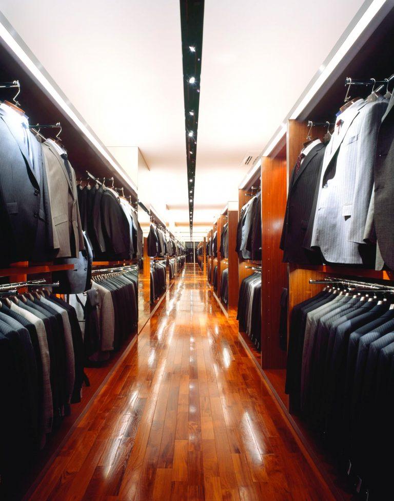 天井に1本のライト埋め込み用のラインが走っている。左右にスーツが整然と陳列されている。手前左上方ネイビースーツ、右隣がグレースーツ。右側上方手前はグレースーツ、左隣はブラックスーツがハンガーにかかっている。