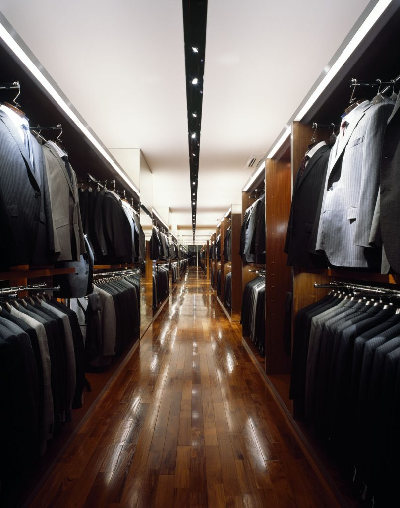 天井に1本のライト埋め込み用のラインが走っている。左右にスーツが整然と陳列されている。手前左上方ネイビースーツ、右隣がグレースーツ。右側上方手前はグレースーツ、左隣はブラックスーツがハンガーにかかっている。  スーツセレクトのスーツの売場。 身長毎に4つのサイズを展開。 黒、紺、グレー、茶色など、様々な色と、無地、ストライプ、チェックなど、様々な柄のスーツが並びます。