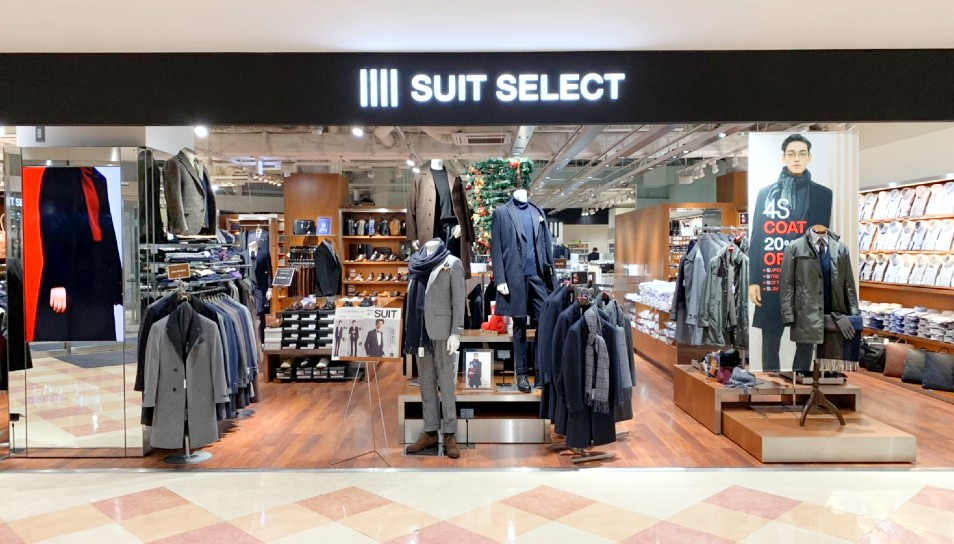 スーツセレクト立川店の店頭。 左から2019-2020AWのデジタルサイネージ。ラックにライトグレーのコート。 正面にはコートのリアルマネキンが2体とスーツにマフラーのリアルマネキンが一体。 向かって右側には4Sコート20%OFFのスクリーンと共に4Sコートが演出。