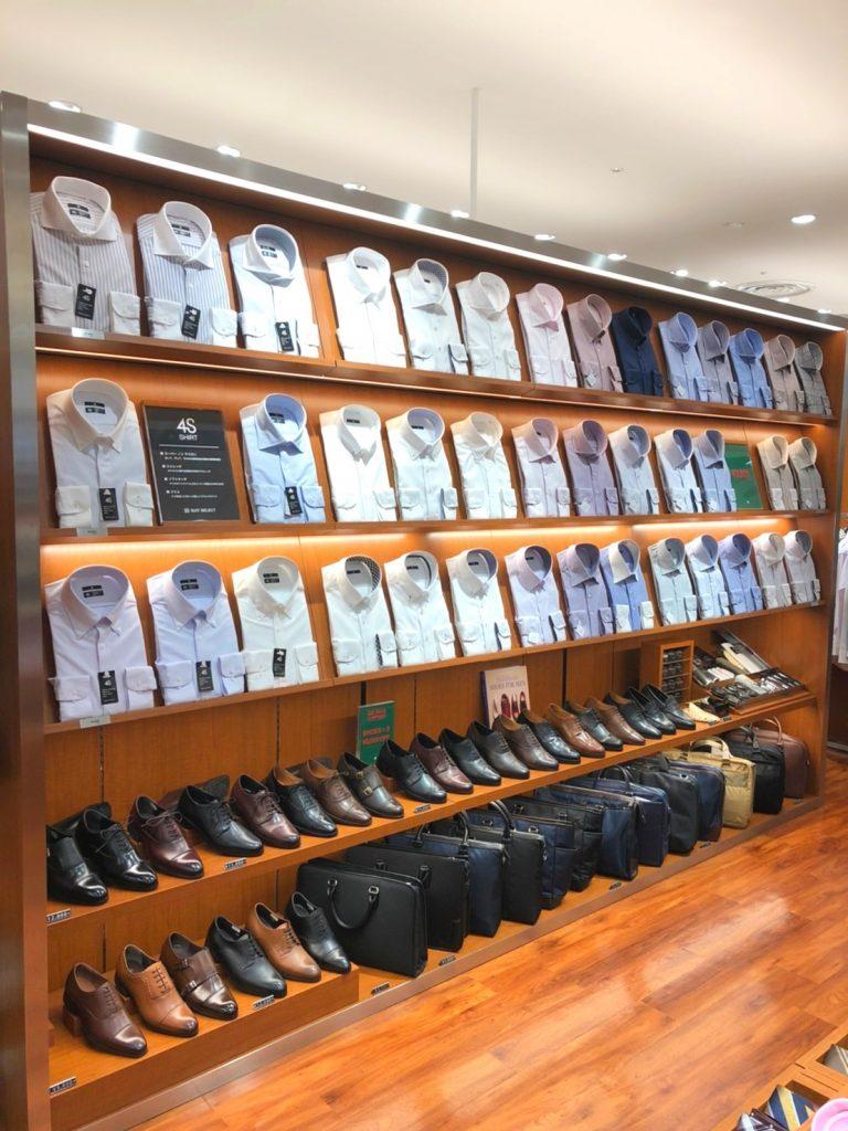 シャツが数多く並んでいる。 白シャツ、サックスブルーのシャツ、ピンクのシャツ、ネイビーのシャツ、パープルのシャツと色が豊富。 レギュラーカラー、ワイドカラー、カッタウェイ、ボタンダウン、ラウンドカラー、ピンホールカラーと襟型も豊富  シャツコーナーの下には靴とバッグが並びます。