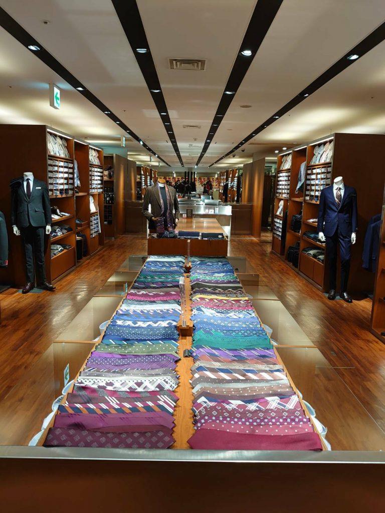 店内中央のネクタイコーナー 色はネイビー、ブルー、グリーン、パープル、バイオレット、ボルドー、ブラウン、ブラック、グレー、イエロー、オレンジなど様々並びます。 柄もソリッド(無地)、レジメンタルストライプ、チェック、ドット、小紋などバリエーション豊富です。