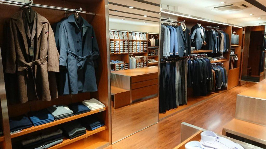 シーズンコーナー 手前にはブラウンとネイビーのウールトレンチコート。 その下の棚には白、紺、青、黒、グレーのニットが並んでいます。 鏡を挟んで、ジャケッとパンツが並びます。