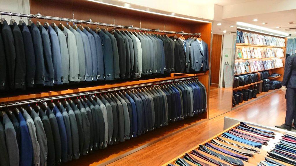 2階スーツコーナー 色の展開はブラック、ネイビー、ブルー、グレー、ブラウン 柄の展開はソリッド(無地)、シャドー柄、ストライプ柄、チェック柄、ハウンドトゥース、グレナカートチェック。 価格が袖のボタンについており、¥18.000、¥28,000、¥38,000が並んでいます。