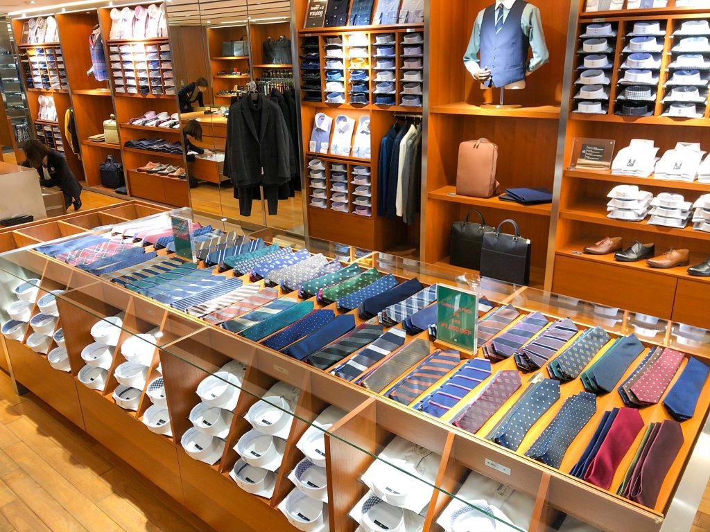 ネクタイコーナーは、手前がブラックラインのやや細めのネクタイ。 奥がシルバーラインの8cm〜9cmのネクタイ。 色柄豊富に陳列されており、 柄は無地、ドット(水玉)、小紋柄、レジメンタルストライプ、チェック。 色はネイビー、パープル、グリーン、イエロー、ボルドー、グレー、ブラック、ブラウンなど