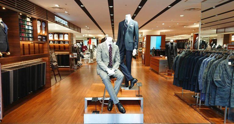 スーツセレクト横浜西口店の店頭イメージ。 正面には2体のリアルマネキンが並びます。 向かって左側にはライトグレーのピークドラペルグレナカートチェックのスーツ。コーディネートにワインカラーをチョイス。 向かって右側にはダークカラーのスリーピーススーツ。コーディネートはスーツと同色をベースにアクセントにパープルの入ったレジメンタルストライプをチョイス。 店頭向かって右側はシーズンコーナーになっており、冬場はコート。夏場は半袖シャツやパンツなどが数多く並びます。 向かって右側はオーダー専門店のディフアレンスがあります。