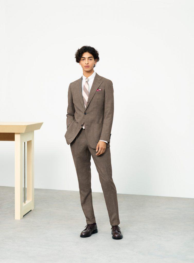 ブラウンのクラシコテーパードのスーツ。インナーに白のタブカラーにライトベージュのレジメンタルタイ