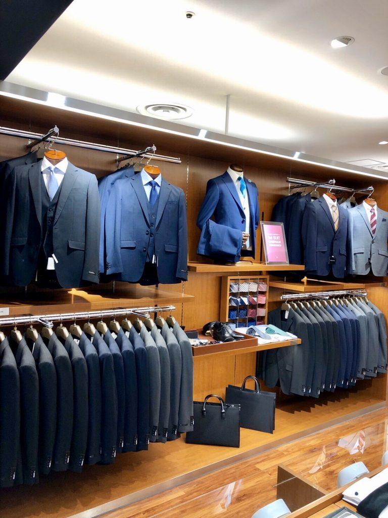 新入学、新入社の方におすすめのフレッシャーズコーナー。 手前からネイビーのスリーピース、ブルーのスリーピース、奥にはネイビーとライトグレーのツーピースが並びます。 中央には全体の着こなしがイメージできるようにスーツの他、シャツ、ネクタイ、バッグ、シューズも並んでいます。