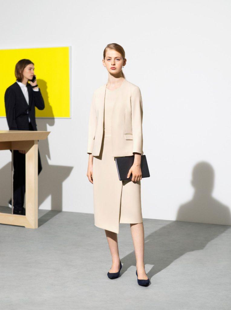 ライトベージュのカセット服。ノーカラーのジャケット。Vネック&フレンチスリーブのトップス。ラップスカート。ダークカラーのクラッチバッグ
