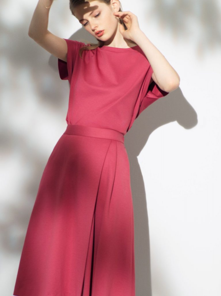 程よいリラックス感のあるオーバーサイズT型トップス(赤色)→シンプルな印象ながら、凝った縫製仕様の袖デザインや、後ろ身頃の切り替え、後ろ下がりの裾デザイン等、様々な着こなしに対応できる1着です。共にのアシンメトリー、ミモレ丈Aラインスカートを着用。