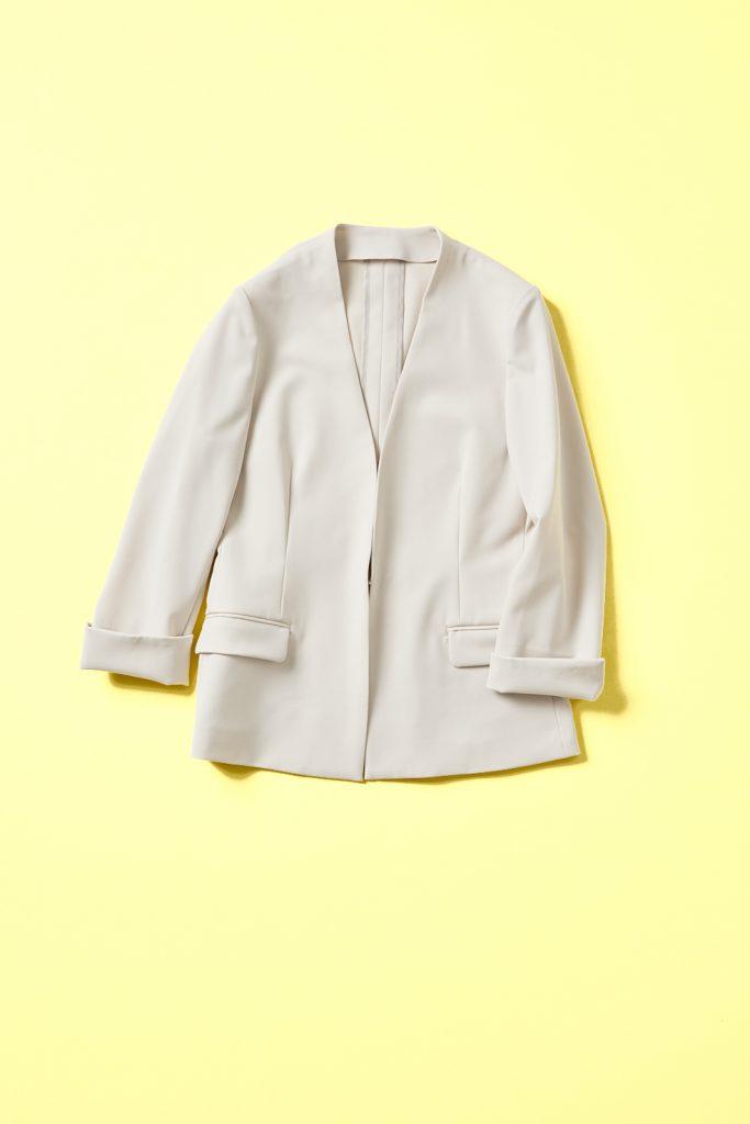 ライトベージュノーカラーのジャケット。フロントホック留めでノームコアなデザインの7分袖(袖口スリット)のジャケット。