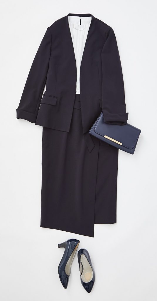 カセット服ネイビーのセットアップ ノーカラーのジャケットにラップスカート。白のフロントギャザーのカットソー。 ネイビーのパンプス
