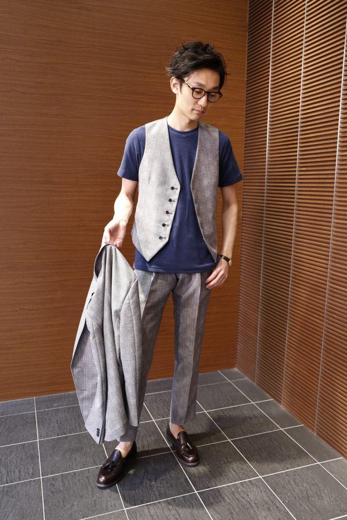ライトグレーグレンチェックスリーピース(セットアップ)インナーにネイビーのTシャツ。ジャケット脱いでるイメージ。シューズはタッセルローファー