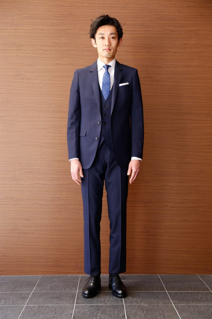 細めのネイビーのウィンドウペーンスリーピーススーツ。白シャツにサックスのネクタイに黒の革靴