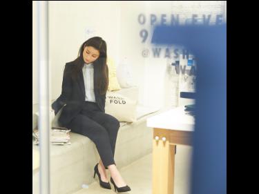 女性がネイビーのスーツに白のカットソーを来て、コインランドリーで雑誌を読んで待っている。