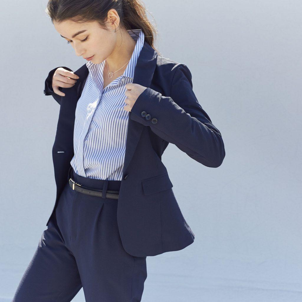 ネイビーのパンツスーツにブルーのストライプシャツを着用した女性が、ジャケットの襟を両手で持っている。
