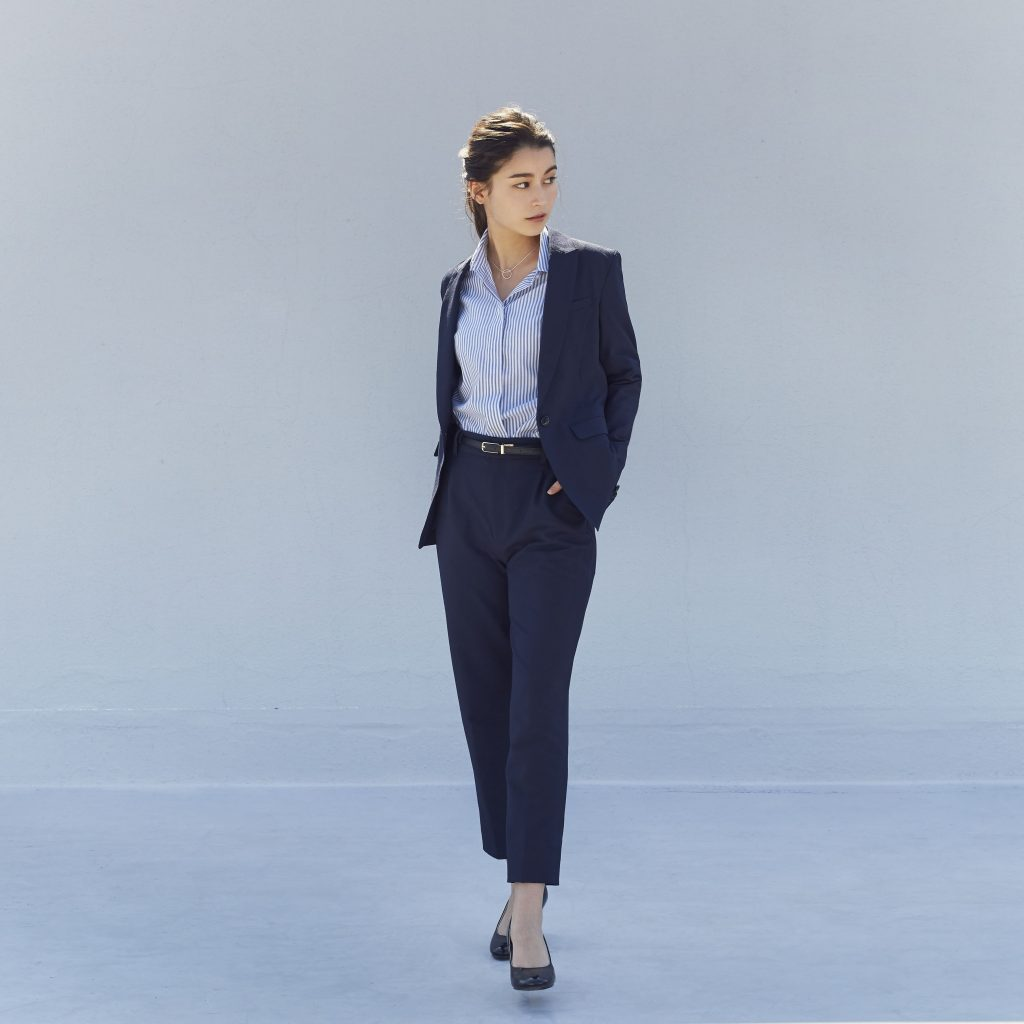 ネイビーのパンツスーツにブルーのストライプのシャツを着た女性が立っている。