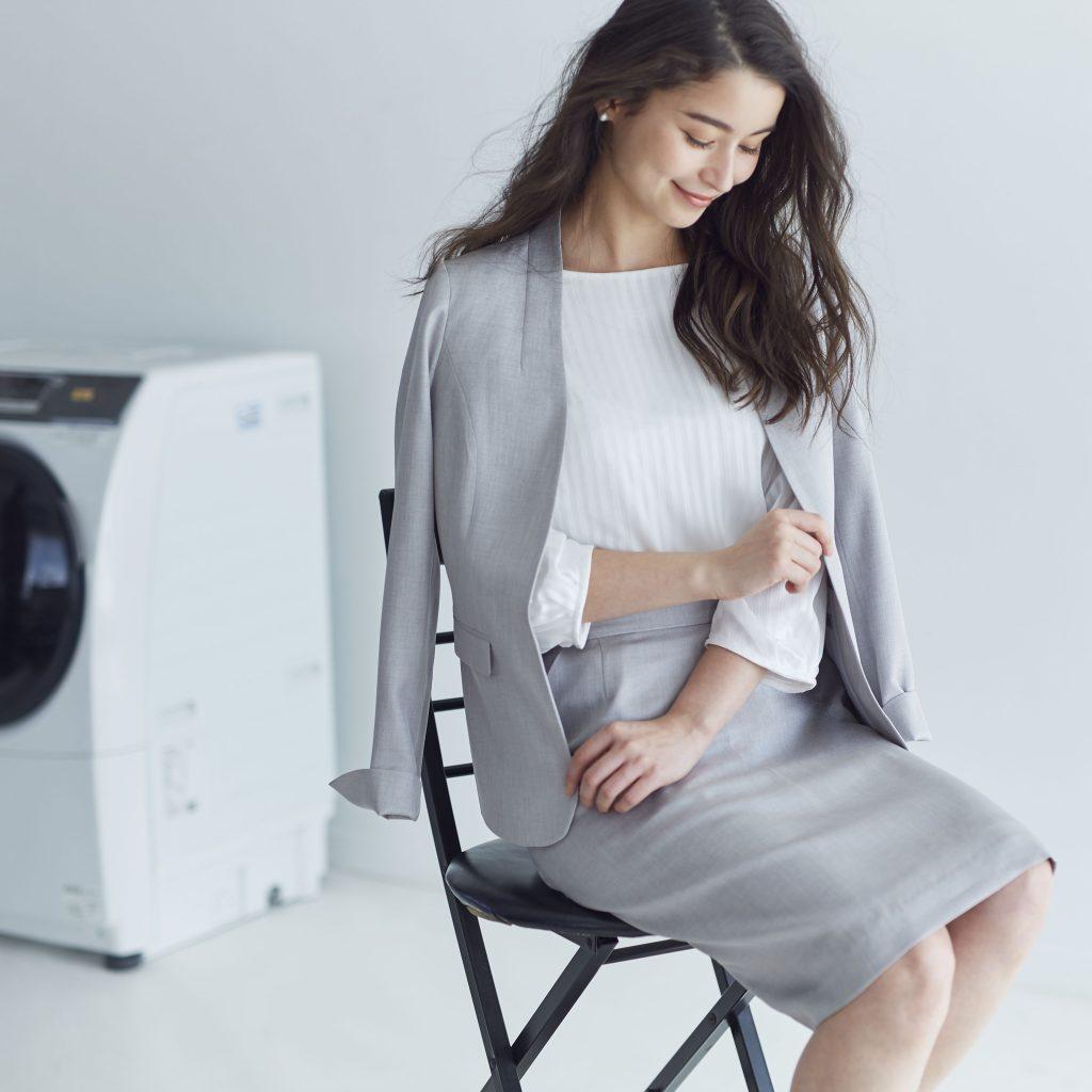 洗濯機の前でライトグレーのノーカラーのスカートスーツを着用した女性が座っている。