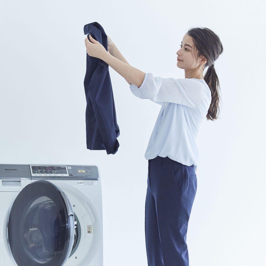 ネイビーのパンツ、白のカットソーを着用した女性が、洗濯したジャケットを手に持っている様子
