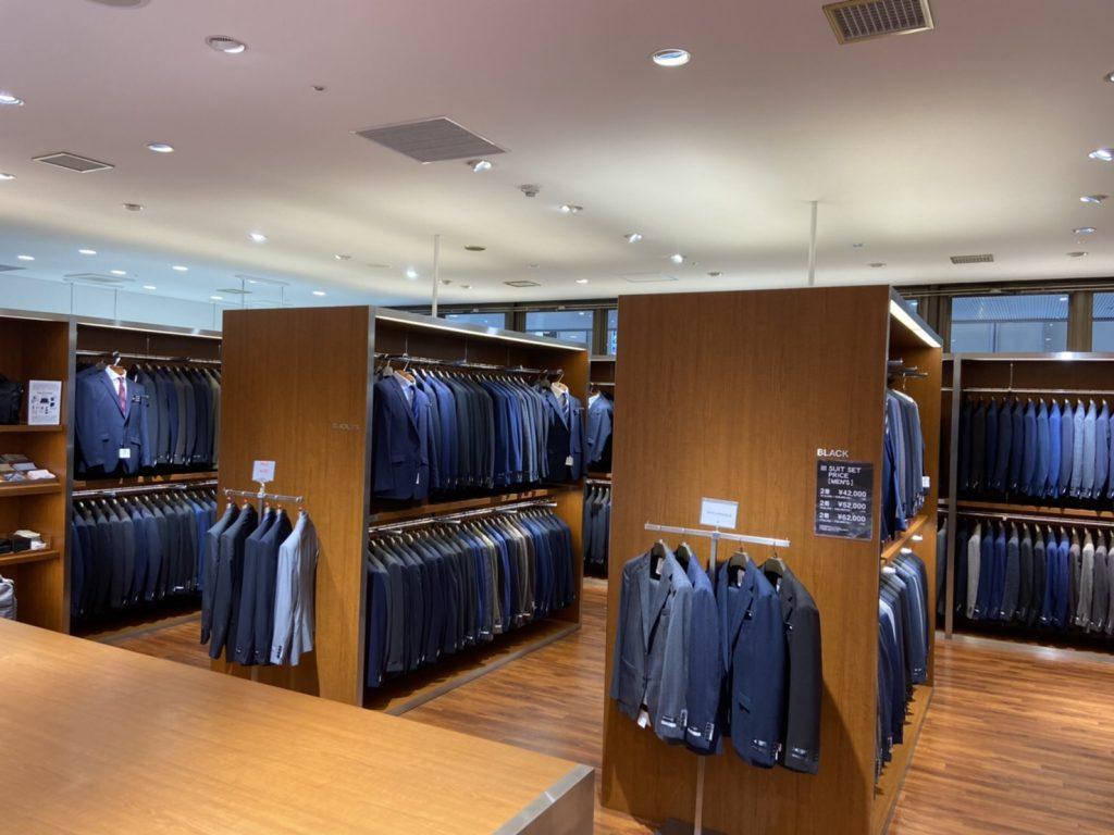 スーツコーナー 黒・紺・グレー・茶色など数多くのスーツが並んでいます。