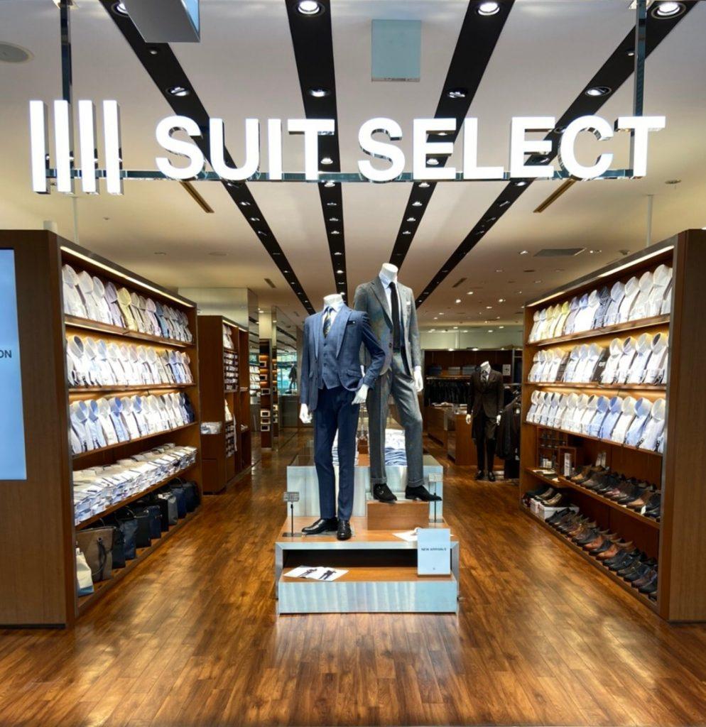 スーツセレクト博多駅前店の店頭。 中央にネイビーとグレーのスーツを着た2体のリアルマネキン。 両サイドは上半分んシャツのクローゼットで下半分はシューズ&バッグコーナー  シャツはホワイト、ブルー、ピンク、グレー、ネイビーなど様々な色が並び、襟型も豊富 シューズはブラックを中心にダークブラウン、ライトブラウンが並びます。 レースアップシューズから紐無しまで  バッグはブリーフバッグからトートバッグまで様々なデザインが並びます。