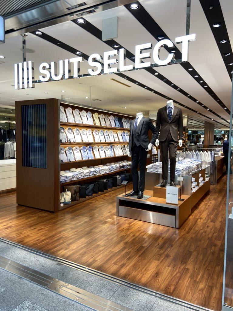 スーツセレクト博多駅前店頭。 正面にはダークカラーのスリーピーススーツとブラウンスーツを着たリアルマネキンがお出迎え。 サイドにはシャツ什器が展開。