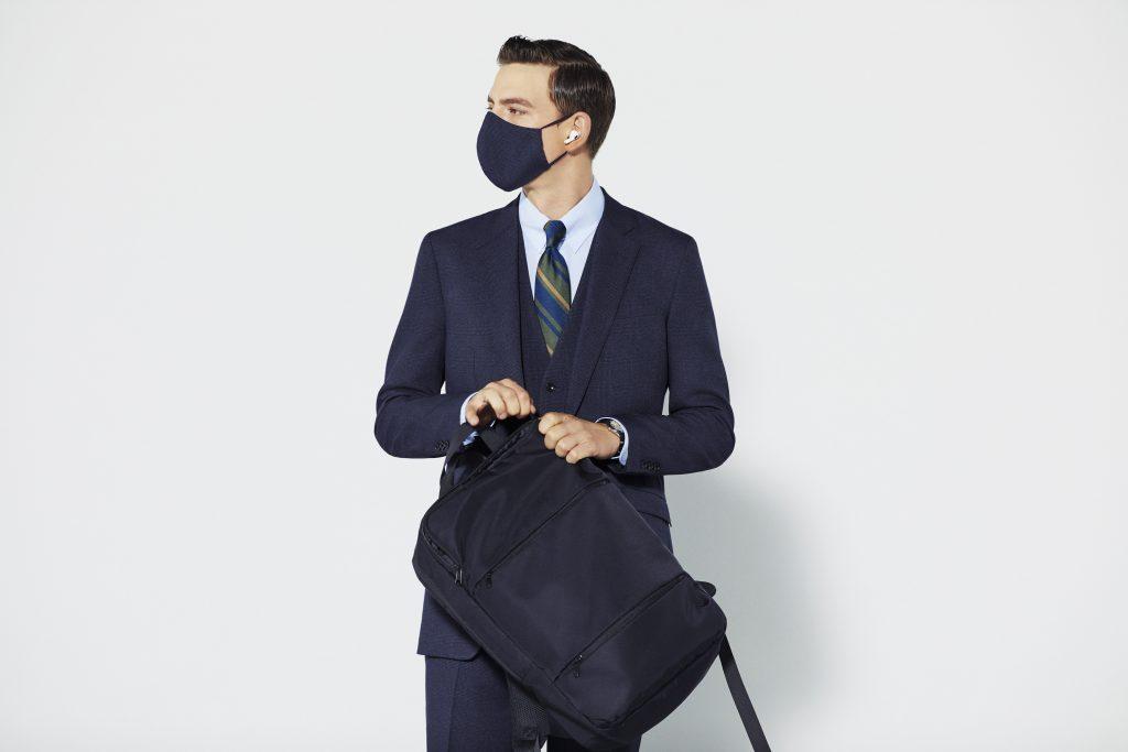 ネイビースーツを着た若者が黒いマスクをつけて、左側を向いている。黒いリュックサックを持っている。