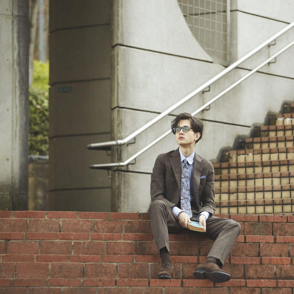 ブラウンのスーツスタイルの男性が、煉瓦作りの階段に腰を下ろしている状態。茶色の靴。茶色の靴下。メガネをかけている。手には本のようなものを携えている。