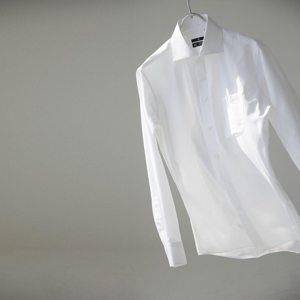ハンガーにかかった白ワイシャツが右側ではためいている。
