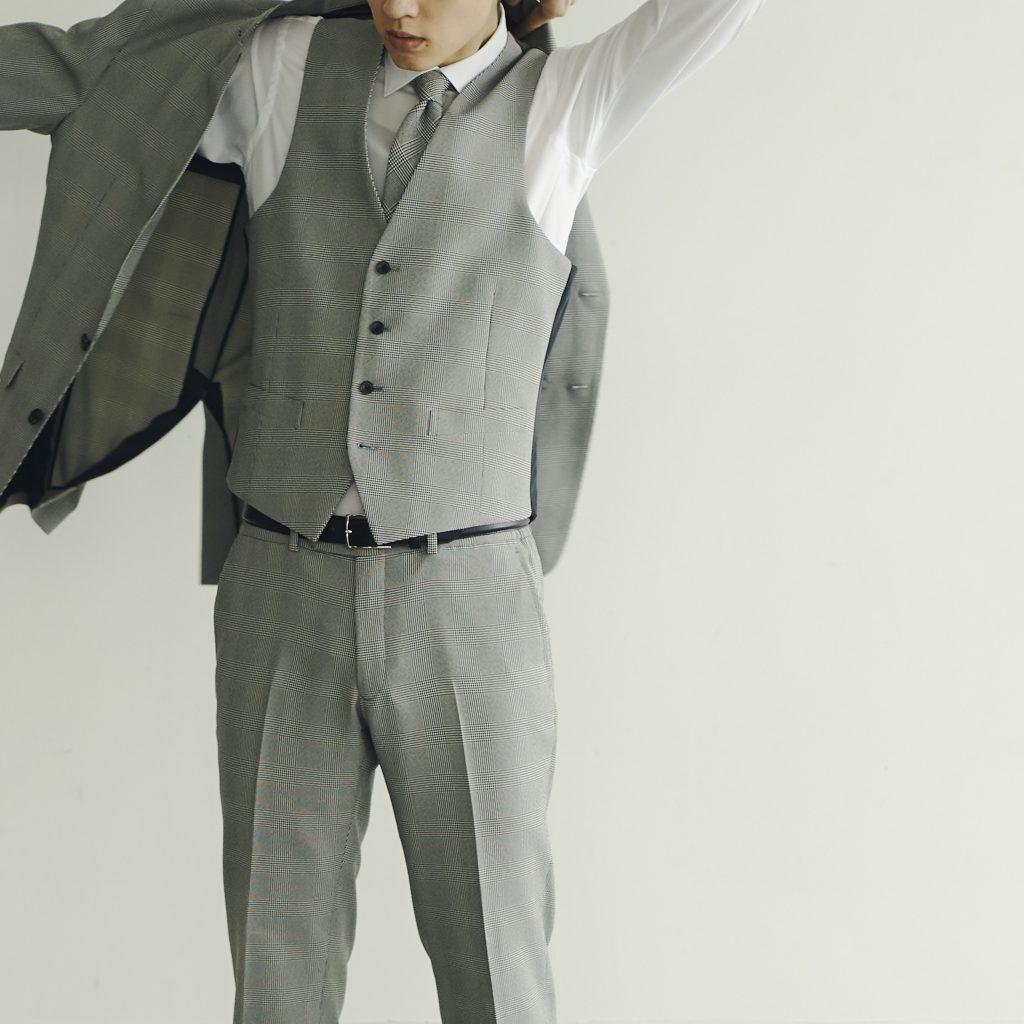 グレー系チェックのスリーピーススーツスタイルの男性が、今まさにジャケットの右腕を通しながら、羽織ろうとしている様子。白ワイシャツにグレーのネクタイ。