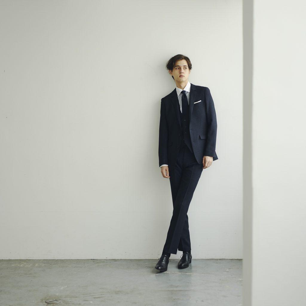 ネイビーのスリーピーススーツスタイルの外国人男性が、右側に立っている。足をクロスして、後ろの壁に寄りかかっているように見える。黒い靴。黒い靴下。