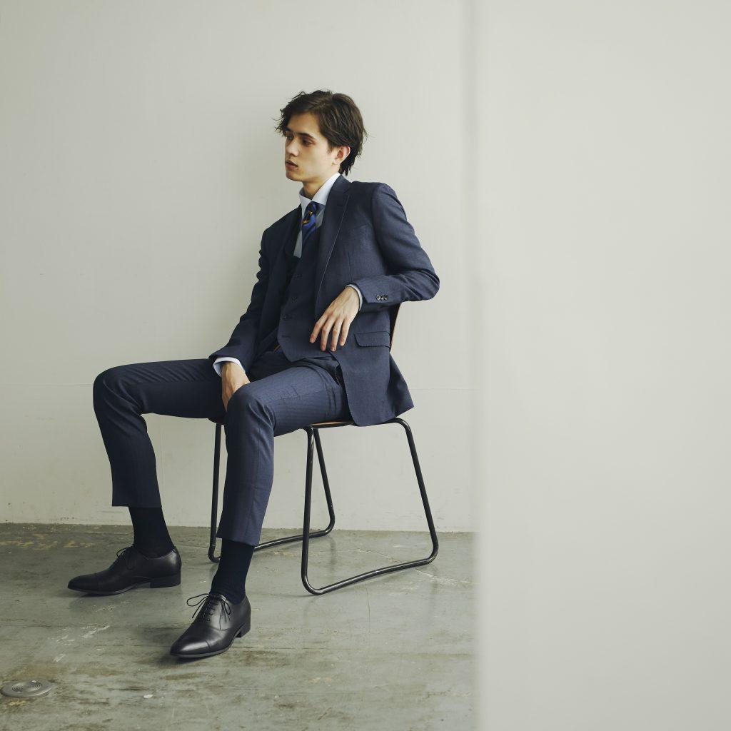 ネイビーのスリーピーススーツを着用した外国人男性が、パイプチェアに腰かけている。黒い靴。黒い靴下。