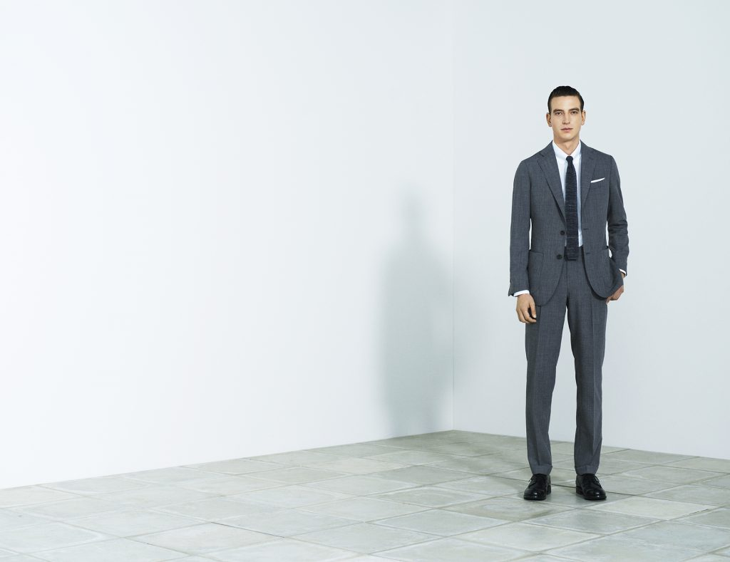 ミディアムグレーのクラシコテーパードのスーツ。 白シャツのダークカラーのニットタイ