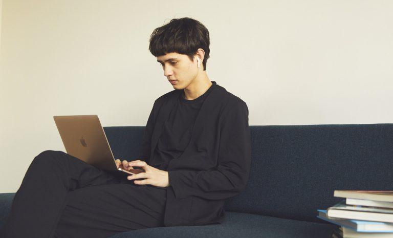 ソファーにPC操作をしている男性が座っている。その男性は、RBCリモートパックスーツ(ブラック・ノーカラー)着用。