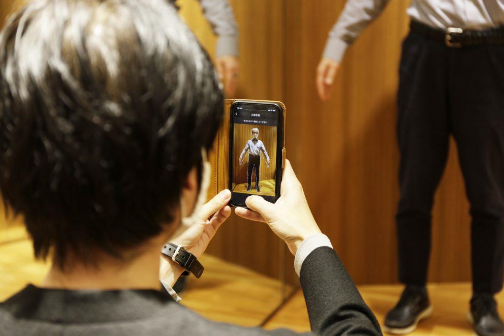 スタッフがお客様にスマホでAI画像採寸アプリを使って採寸