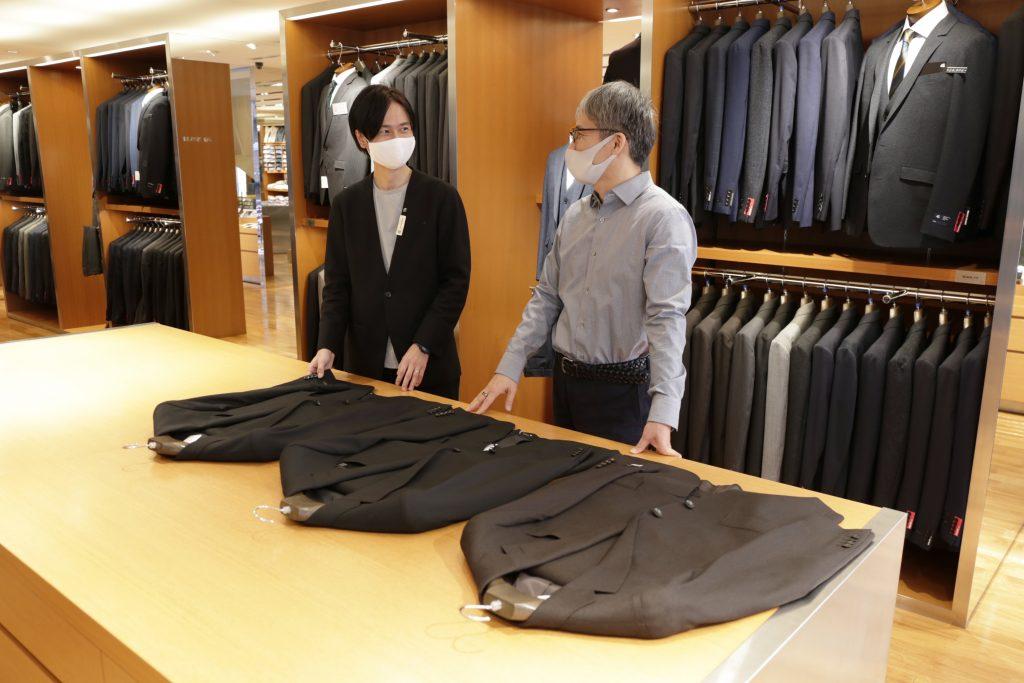 スタッフがお客様にスーツの型紙の違いを説明。 スキニー、ブラックライン、クラシコテーパードのスーツをファンステージにおいて説明。