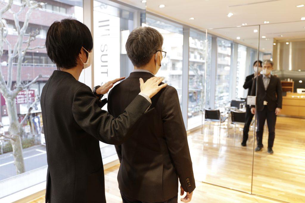 AIスピードオーダースーツの採寸。実際の肩幅などの確認?を鏡の前で接客している画像。