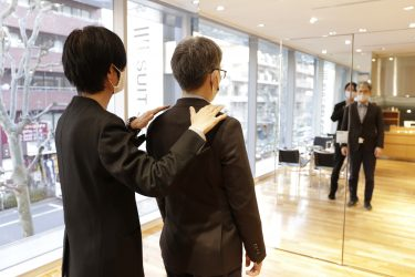ブラックのスーツ着た店員がお客様を接客中。鏡越しにフィッティング中