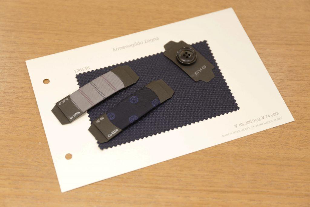 ゼニアのトラベラーの生地カード。 それに合わせた、グレー地にストライプの袖裏生地、胴裏はネイビーの小紋、ボタンはダークネイビーのボタン
