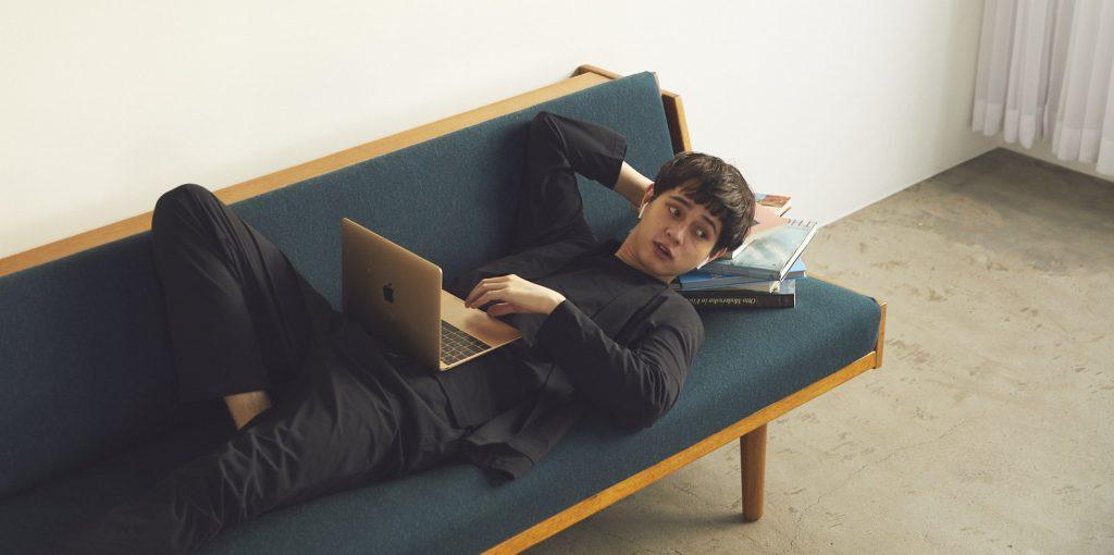ソファーに男性が仰向けに寝転がってPCを操作している